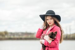 Fille dans un manteau rose et un chapeau noir avec un petit chien Images stock
