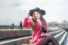 Fille dans un manteau rose et un chapeau noir avec un petit chien photographie stock