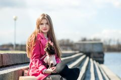 Fille dans un manteau rose et un chapeau noir avec un petit chien Photographie stock libre de droits