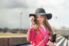 Fille dans un manteau rose et un chapeau noir avec un petit chien Photo stock