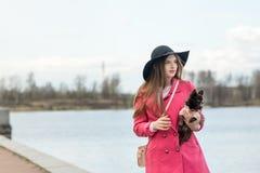 Fille dans un manteau rose et un chapeau noir avec un petit chien Photos libres de droits