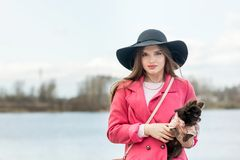 Fille dans un manteau rose et un chapeau noir avec un petit chien Photo libre de droits