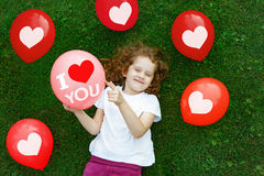 Fille dans un T-shirt blanc tenant un ballon coloré Photographie stock libre de droits