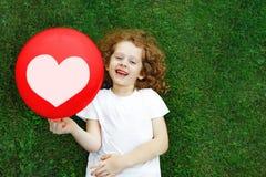 Fille dans un T-shirt blanc tenant un ballon rouge, se trouvant sur la pelouse Images libres de droits