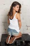 Fille dans un T-shirt, des espadrilles et des shorts se reposant avec le sien de nouveau à l'appareil-photo Mur de briques blanc, Image stock