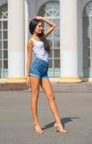 Fille dans un T-shirt et shorts devant un bâtiment avec des colonnes Photographie stock libre de droits