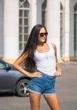 Fille dans un T-shirt et shorts devant un bâtiment avec des colonnes Photographie stock