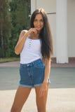 Fille dans un T-shirt et shorts devant un bâtiment avec des colonnes Photo libre de droits