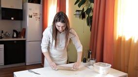 Fille dans un tablier préparant la pâte crue de pizza La fille prépare une pizza délicieuse à la maison pâtisserie banque de vidéos