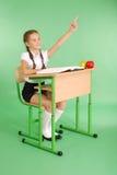 Fille dans un uniforme scolaire soulevant la main pour poser la question Photos stock