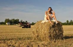 Fille dans un vêtement rural se reposant sur la meule de foin Image libre de droits