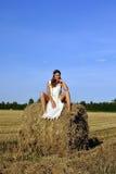 Fille dans un vêtement rural se reposant sur la meule de foin Images libres de droits