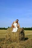 Fille dans un vêtement rural se reposant sur la meule de foin Photos stock