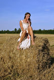 Fille dans un vêtement rural se reposant sur la meule de foin Image stock