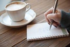 Fille dans une écriture de café dans un carnet photo stock