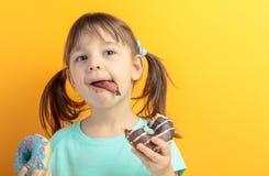 Fille dans une chemise de turquoise manger des butées toriques photo stock