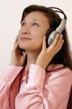 Fille dans une chemise rouge avec des écouteurs Photographie stock libre de droits