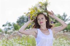 Fille dans une guirlande des champ-fleurs Photographie stock libre de droits