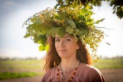 Fille dans une guirlande des feuilles et des fleurs de chêne Symbole de l'unité avec la nature photos libres de droits