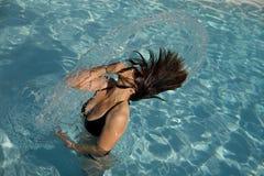 Fille dans une piscine projetant le cheveu humide Photographie stock libre de droits