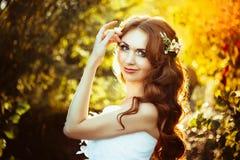 Fille dans une robe blanche au coucher du soleil Photos stock