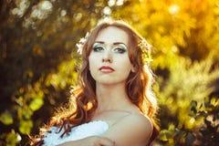 Fille dans une robe blanche au coucher du soleil Image stock
