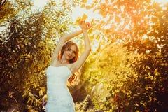 Fille dans une robe blanche au coucher du soleil Images stock