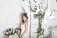Fille dans une robe blanche avec des fleurs dans la maison images libres de droits