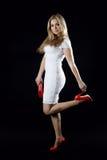 Fille dans une robe blanche, des chaussures rouges et un sac d'embrayage rouge Image libre de droits