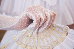 Fille dans une robe blanche luxuriante et dans les gants blancs avec la belle fan de main photos libres de droits