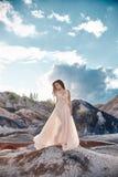 Fille dans une robe bleu-clair tenant dans le vent avec des montagnes i Photographie stock libre de droits