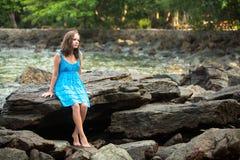 Fille dans une robe bleue dans les roches du voyage de côte Photographie stock