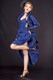 Fille dans une robe bleue sur un fond noir Images stock