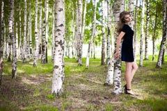 Fille dans une robe dans une plantation de bouleau Photos libres de droits