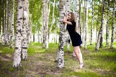 Fille dans une robe dans une plantation de bouleau Images stock