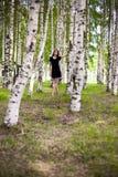 Fille dans une robe dans une plantation de bouleau Photos stock