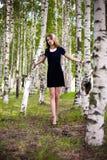 Fille dans une robe dans une plantation de bouleau Photographie stock libre de droits