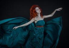 Fille dans une robe en soie, une belle danse rousse de fille dans un vol de robe de long vert dans le ciel, une robe de long vert Photo libre de droits