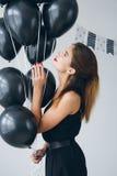 Fille dans une robe noire avec les ballons noirs Photographie stock