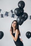 Fille dans une robe noire avec les ballons noirs Photos libres de droits