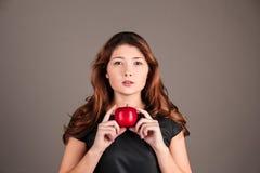 Fille dans une robe noire avec une pomme Image mystérieuse image libre de droits