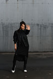 Fille dans une robe noire posant dans le parking Photographie stock