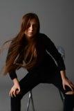 Fille dans une robe noire posant sur une chaise dans le studio sur un fond gris Photographie stock