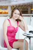 Fille dans une robe rose avec un téléphone portable Images libres de droits