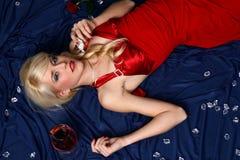 Fille dans une robe rouge avec une glace de vin Images libres de droits