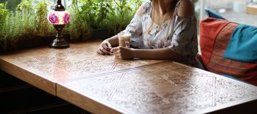 fille dans une robe se reposant à une table dans un café et un café potable, attendant une réunion, une date photos stock