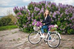 Fille dans une veste en cuir près de la bicyclette blanche Photographie stock libre de droits