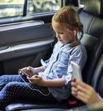 Fille dans une voiture utilisant un dispositif numérique photo libre de droits