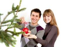 Fille décorant l'arbre de Noël avec le type au hom Image stock