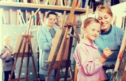 Fille de aide de professeur féminin pendant la classe de peinture image libre de droits
